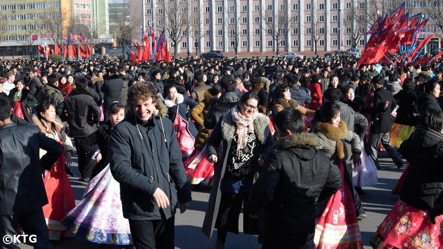 Un membre du personnel de KTG en train de danser avec les Coréens pendant l'anniversaire de Kim Jong Il à Pyongyang, Corée du Nord (RPDC)