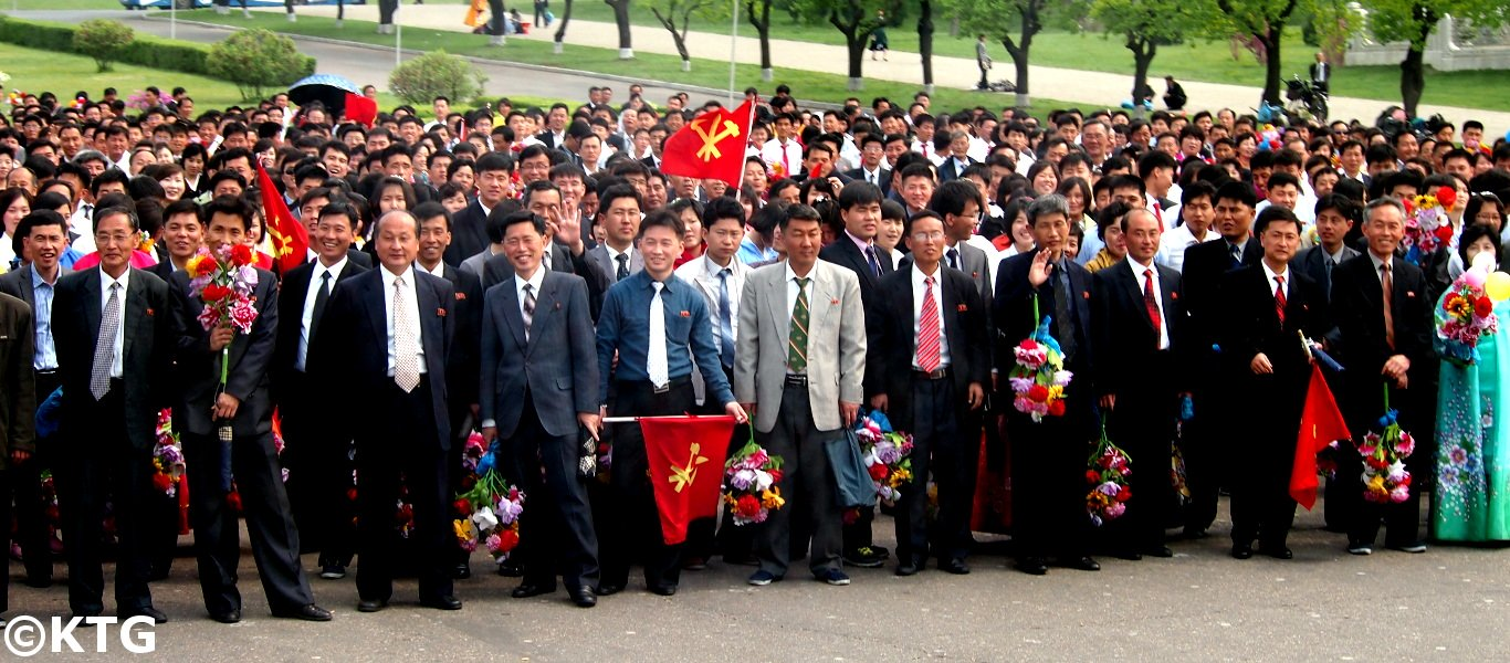 North Koreans with the party flag