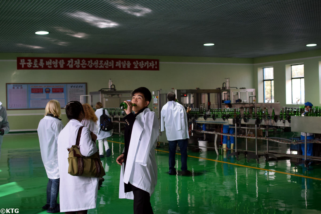 North Korean university student drinking water at the Kangso mineral water bottling factory near Nampo city, North Korea (DPRK). Trip arranged by KTG Tours