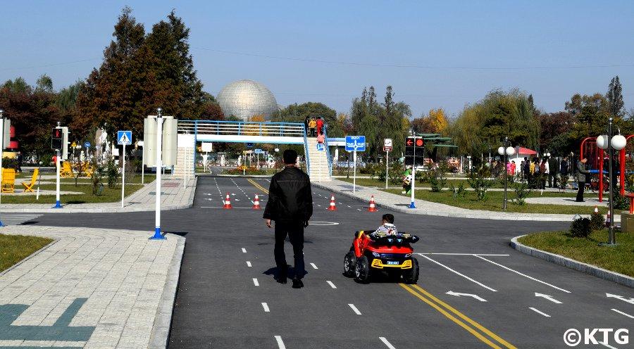 Enfant conduisant une petite voiture au parc de la circulation des enfants de Pyongyang, Corée du Nord (RPDC)