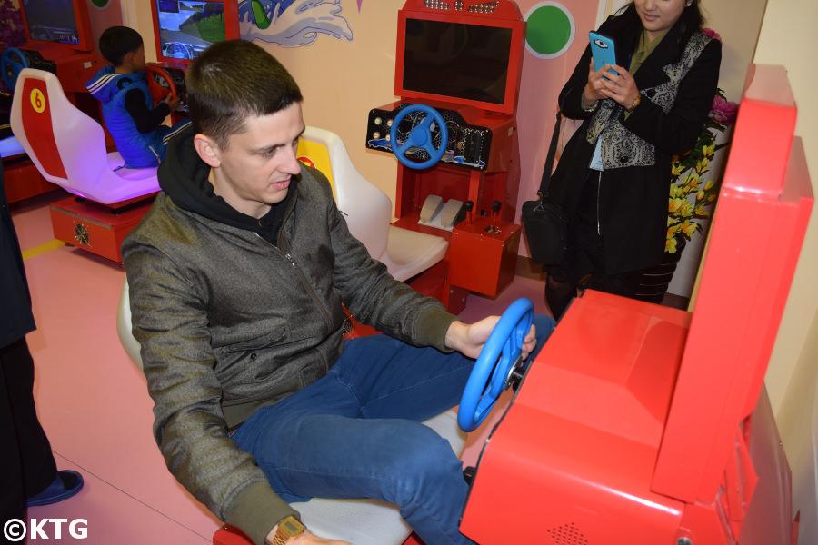 Rayco de KTG Tour conduisant un simulateur de voiture au parc pour enfants de Pyongyang, Corée du Nord (RPDC)
