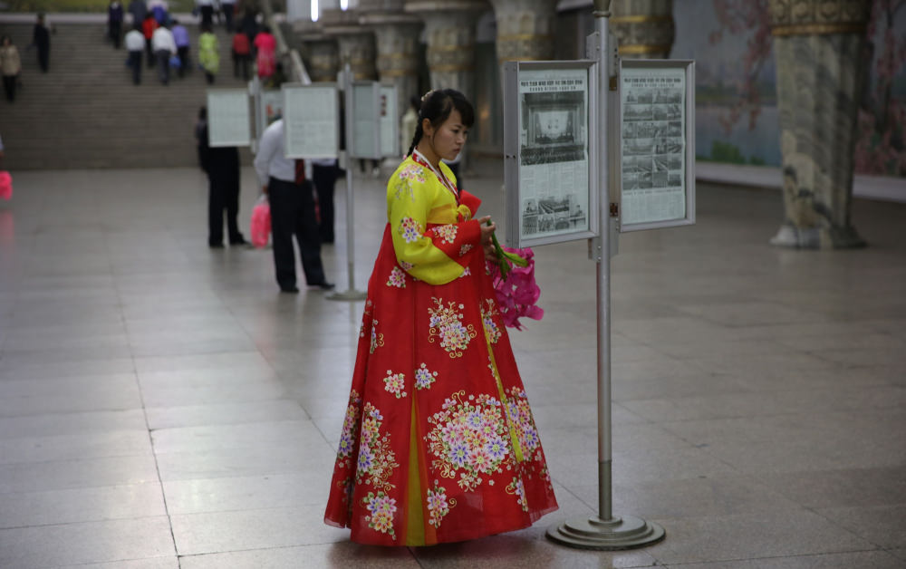 North Korean lady reading a framed newspaper in the Pyongang metro, DPRK