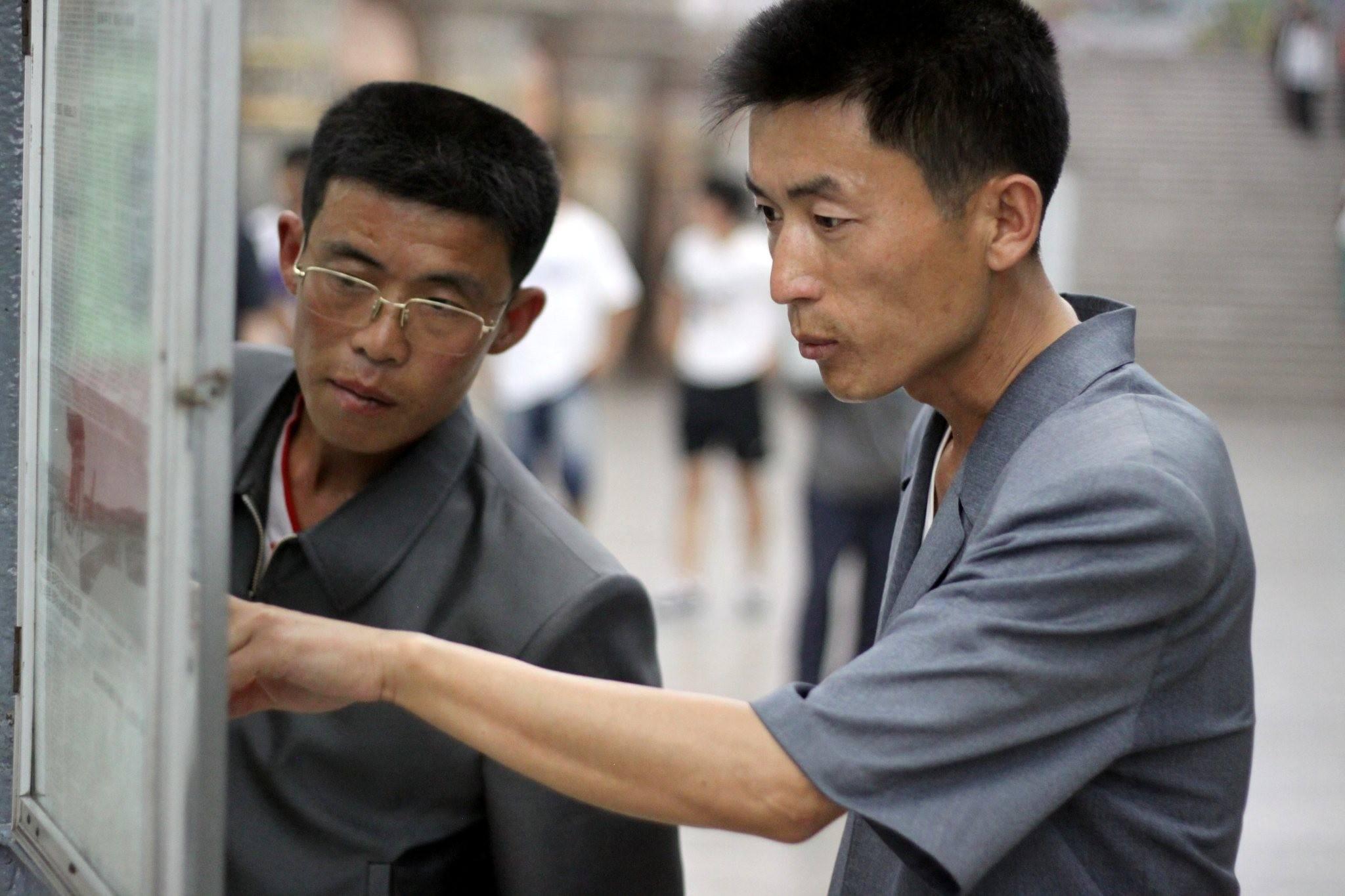 Norcoreanos leyendo el periódico en el metro de Pyongyang. Viaje organizado por KTG Tours