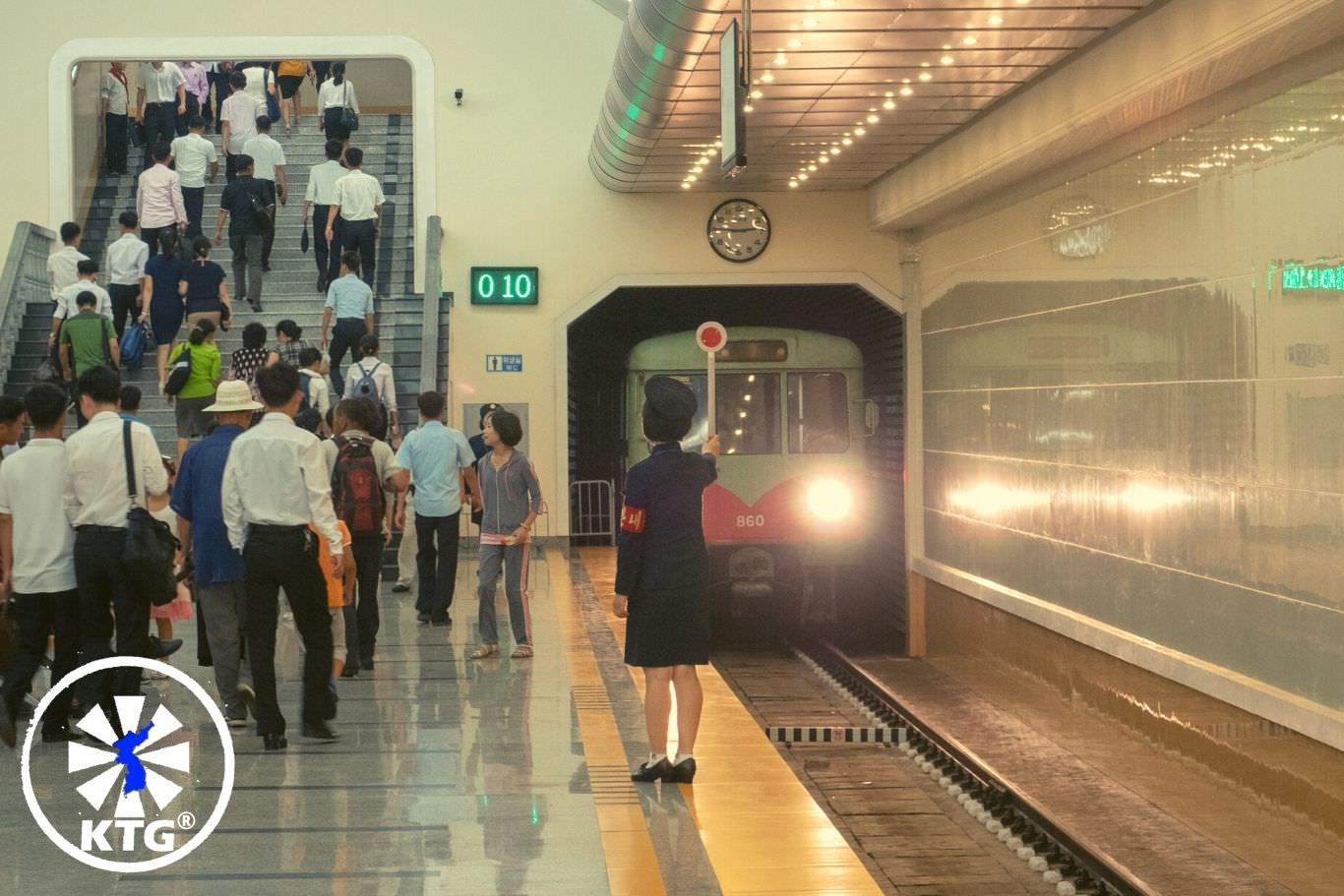 Passengers at a metro stop in Pyongyang, North Korea. Tour arranged by KTG®