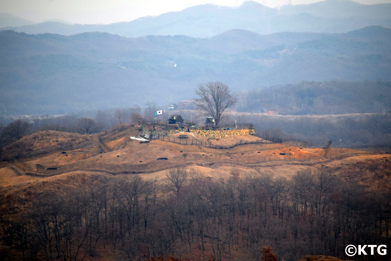 South Korean military post across the DMZ seen from North Korea. You can see the UN and South Korean flags fluttering in the wind. Trip arranged by KTG to see the Concrete Wall from Kaesong in North Korea