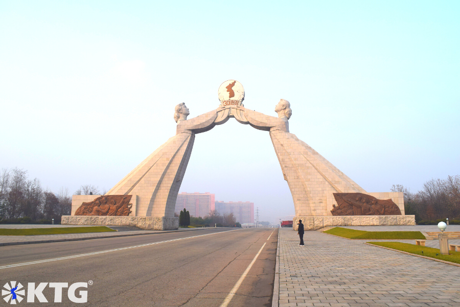 KTG traveller taking a photo of the arch of reunification in Pyongyang, North Korea, DPRK. The Monument to Three Charters for National Reunification symbolises the reunification of Korea and was built in 2001.