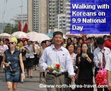 North Koreans walking towards a military parade in Pyongyang with KTG western travellers